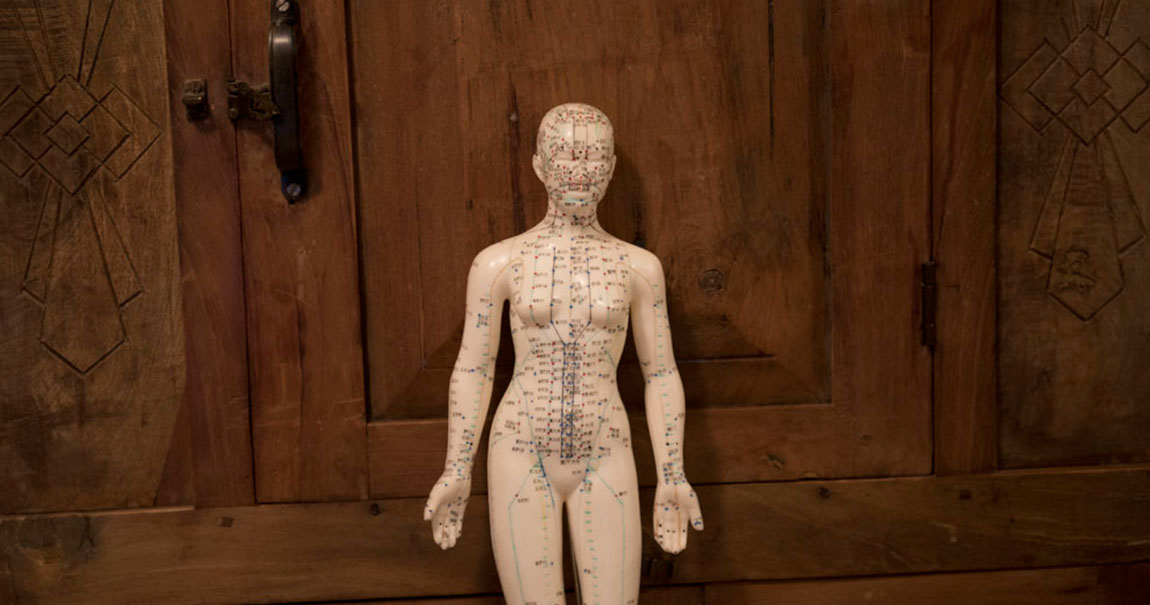 A map of acupuncture points printed onto a small female figurine.