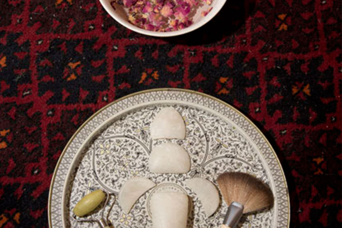 An array of quartz facial tools, a jade face roller, and fan brush on a tray next to a bowl of rose petals.